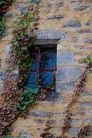 Beautiful shot of ivy creeping up a stone wall with wrought iron window.