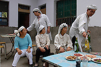 Mourning -hence the white color-in a christian family for the first anniversary of the passing of a family elder near Xi'an, Shaanxi province, China.
