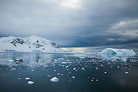 Glacier and mountains with icebergs on a calm sea under dark clouds, Antarctica. Seascapes and icescapes photography wall art. Fine art photography prints.