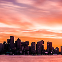 Panoramic Boston skyline sunset photo. The sky is a beautiful shade of purple and orange as the sun sets over Boston Harbor. Panoramic photo ratio is 1:3.