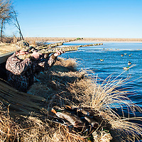 duck hunters shooting over water from blind