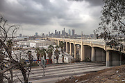 Los Angeles, California, U.S. - <br /> <br /> Life On The Edge<br /> <br /> According to the Los Angeles Homeless Services Authority, the homeless population of Los Angeles and L.A. County has increased as much as 20% in the last year, and leads the nation in homeless unsheltered living, at nearly 70%.<br /> Homelessness here has grown substantially since the last El Niño, which dumped 30 inches of rain on Los Angeles during the winter of 1997-98, authorities say. Recently, the Los Angeles City Council declared a state of emergency on homelessness and called for $100 million to help address the growing crisis. The Los Angeles River flows through Los Angeles County, from Canoga Park in the western end of the San Fernando Valley, nearly 48 miles southeast to its mouth in Long Beach. Homeless people live along much of its length, with many located generally east of Downtown L.A., making their homes in and around the river, under overpasses or alongside rail lines and industrial wastelands. Those people - many dealing with disability, mental health and criminal justice issues - living in tents, improvised shelters and live-in vehicles, have increased 85% in the same period. Causes include high unemployment, low wages and escalating rents, coupled with gentrification and elimination of SRO hotels and cheap rooms, a last option for many. An estimated 800 people live in LA's riverbeds and storm drains, which will be deluged with powerful torrents when El Niño storms arrive in early 2016. Although the Sheriff's Department and LA's Homeless Services Authority have made numerous visits to warn residents, many see no compelling reason - or options - for moving. Most are not the transient homeless we are used to seeing but have set up semi-permanent living quarters in the LA River, which with its sweeping concrete vistas and city skyline sunsets may soon become both a beautiful and dangerous place to call home.<br /> <br /> The view from a brush-covered hill as the 6th Street B
