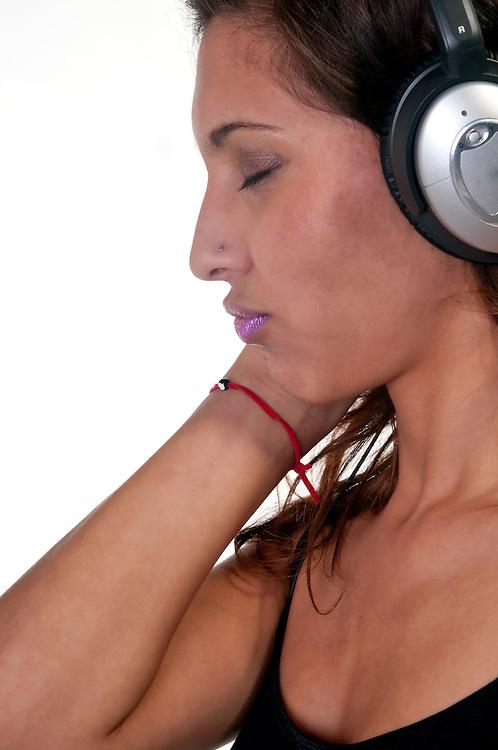 Portrait of hispanic girl listening music with headphones.