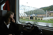 Romania, woman sits in train passing through the countryside