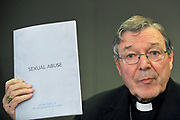 Cardinal George Pell holds up a folder outlining the archdiocese response to sexual abuse at a press conference in Sydney, Australia.