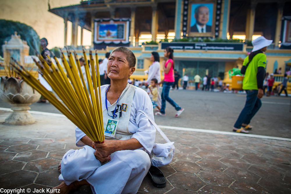 "30 JANUARY 2013 - PHNOM PENH, CAMBODIA: A Cambodian woman wearing white mourning clothing burns incense for late Cambodian King Norodom Sihanouk in Phnom Penh. Sihanouk (31 October 1922 - 15 October 2012) was the King of Cambodia from 1941 to 1955 and again from 1993 to 2004. He was the effective ruler of Cambodia from 1953 to 1970. After his second abdication in 2004, he was given the honorific of ""The King-Father of Cambodia."" Sihanouk held so many positions since 1941 that the Guinness Book of World Records identifies him as the politician who has served the world's greatest variety of political offices. These included two terms as king, two as sovereign prince, one as president, two as prime minister, as well as numerous positions as leader of various governments-in-exile. He served as puppet head of state for the Khmer Rouge government in 1975-1976. Most of these positions were only honorific, including the last position as constitutional king of Cambodia. Sihanouk's actual period of effective rule over Cambodia was from 9 November 1953, when Cambodia gained its independence from France, until 18 March 1970, when General Lon Nol and the National Assembly deposed him. Upon his final abdication, the Cambodian throne council appointed Norodom Sihamoni, one of Sihanouk's sons, as the new king. Sihanouk died in Beijing, China, where he was receiving medical care, on Oct. 15, 2012. His cremation is scheduled to take place on Feb. 4, 2013. Over a million people are expected to attend the service.        PHOTO BY JACK KURTZ"