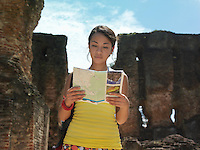Young woman reading guide book ancient ruins in background