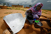 Iriba, -, TCD, August 22nd 2007: A woman pours tea boiled in the solar oven (right) in the Iridimi refugee camp. 8600 families in this refugee camp now use the solar oven, manufactured on site by the Chad Sun company. The oven, which is basicaly a parabol made from cardboard and aluminum foil concentrating the heat on a black painted pan inside a sealed plastic bag, is the brain child of the Swiss naturalist Horace de Saussure. When Marie Rose Neloum first saw the oven in action, she immediately saw the potential. She now runs the project in Touloum, Iridimi and in several other refugee camps.<br /> The benefit from using the oven are both obvious and also surprising. Besides being emission free it also saves the women from the risky and daunting task of gathering firewood.<br /> The increasing population of refugees in the camps have widened the radius of the area where the refugee women have to look for firewood, exposing the women to the risk of rape.
