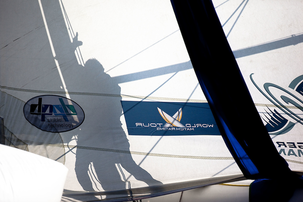 A bowman casts a shadow on the jib as he bounces the spinnaker halyard during day 2 of Match Race Germany. World Match Racing Tour. Langenargen, Germany. 21 May 2010.