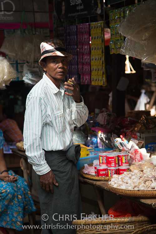 Man smoking a cheroot (Burmese cigar) while waiting in a market in Bagan, Myanmar.