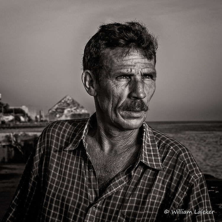 Man looks out at the water along the Malecon.