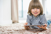 Portrait of happy boy with digital tablet lying on rug at home