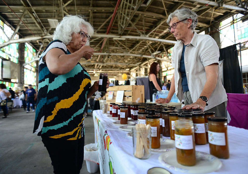 apl050717f/ASECTION/pierre-louis/JOURNAL 050717<br /> Petrita Maldonado,, left , samples jams and jellies  being sold by Addie Draper ,, of Mountainair  at the Railyards Market . The popular event runs through the last Sunday of October .Photographed on Sunday May 7 2017. .Adolphe Pierre-Louis/JOURNAL
