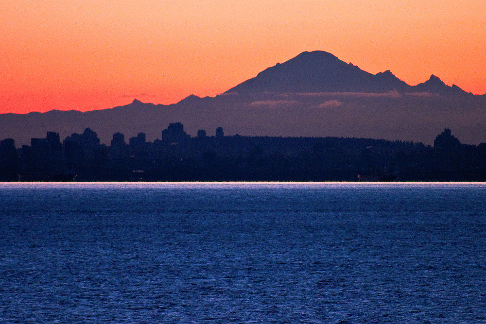Mount Baker Washington rises above Vancouver BC skyline, English Bay and West End in foreground