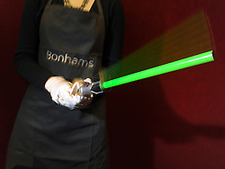 © Licensed to London News Pictures. 08/12/2011, London, UK. A Bonhams employee holds a prop Light Saber used by Ewan McGregor as Obi-Wan Kenobi in the film Star Wars: The Phantom Menace. The prop is expected to fetch 18,000-20,000 GBP.  Bonhams, London, photocall for entertainment memorabilia today, 8th December 2011.The auction takes place on Thursday 15th DecemberPhoto credit : Stephen Simpson/LNP