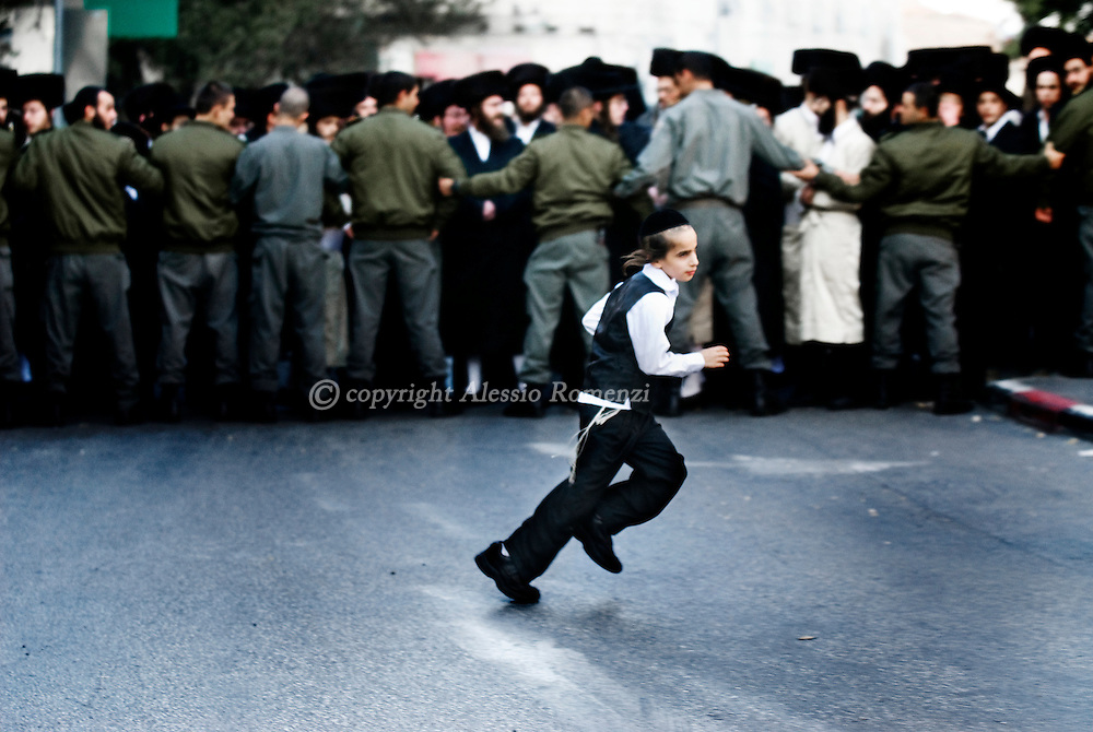 A Jewish man child run beind of a line of Israeli border policemen in Mea Sharim, in Jerusalem, Saturday, Nov. 21, 2009. Ultra-Orthodox Jews have been protesting against a decision by secular Mayor Nir Barkat to open the car park on the Sabbath, the Jewish day of rest which runs from Friday sundown to Saturday sundown..© ALESSIO ROMENZI