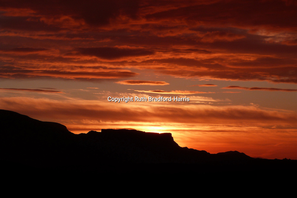 A spectacular sunset over the distinctive silhouette of Leac nan Fionn ('Fingal's Table'), Quiraing, Trotternish Ridge, from Valtos, Isle of Skye.<br />