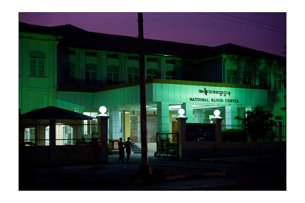 SMALL version - 9&quot;X6&quot; (23X15 cm) <br /> A couple walks next to the National Blood Center at night in Yangon. A set of special edition prints on offer at a special price to raise money for the earthquakes that devastated Central Italy and Central Myanmar at the end of August 2016. Each print comes with a wide border on fine-art paper ready to be framed on standard size mounts. <br />  I will donate all profits to charities helping the victims of the earthquakes.