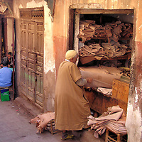 Undyed Leather Merchant in Marrakech, Morocco<br /> Aficionados of leather will be enthralled with the souks in Marrakech.  Follow your nose &ndash; literally &ndash; towards the smelly tanneries to see how hides are soaked in lime, then cured in bird excrement and colored in dye before drying. Merchants like this one sell bolts of undyed leather primarily to local craftsmen.  Countless other vendors offer a dizzying display of finished goods such as handbags, belts and clothes. The best price comes through unrelenting bargaining.  But also purchase away from other tourists and while wearing nothing flashy or expensive.