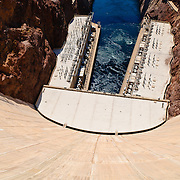 Looking down from the top of the massive concrete wall of the Hoover Dam. At top is the outflow of the Colorado River with the twin buildings housing the hydroelectric turbines on either side of the river. The dam spans the state border, with Arizona on the left and Nevada on the right.