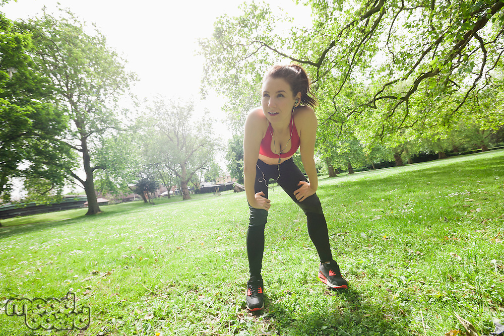 Full length of tired fit woman taking break while exercising in park