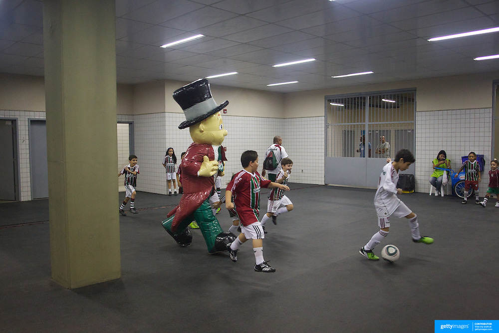 The Fluminense mascot plays football with young fans near the players dressing rooms inside the stadium. The youngsters were waiting to form a guard of honour for the players  before the Fluminense V Atletico MG, Futebol Brasileirao  League match at Estadio Olímpico Joao Havelange, Rio de Janeiro. Fluminense won the match 5-1. Rio de Janeiro,  Brazil. 23rd September 2010. Photo Tim Clayton