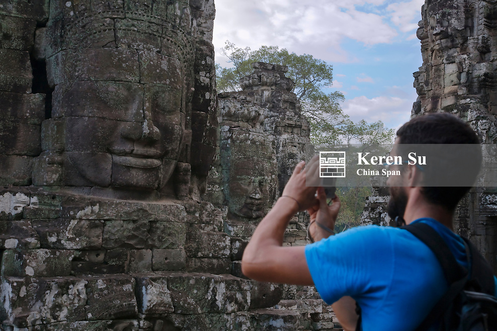 Tourist photographing Buddhist statues at Bayon Temple, Angkor Thom, UNESCO World Heritage site.