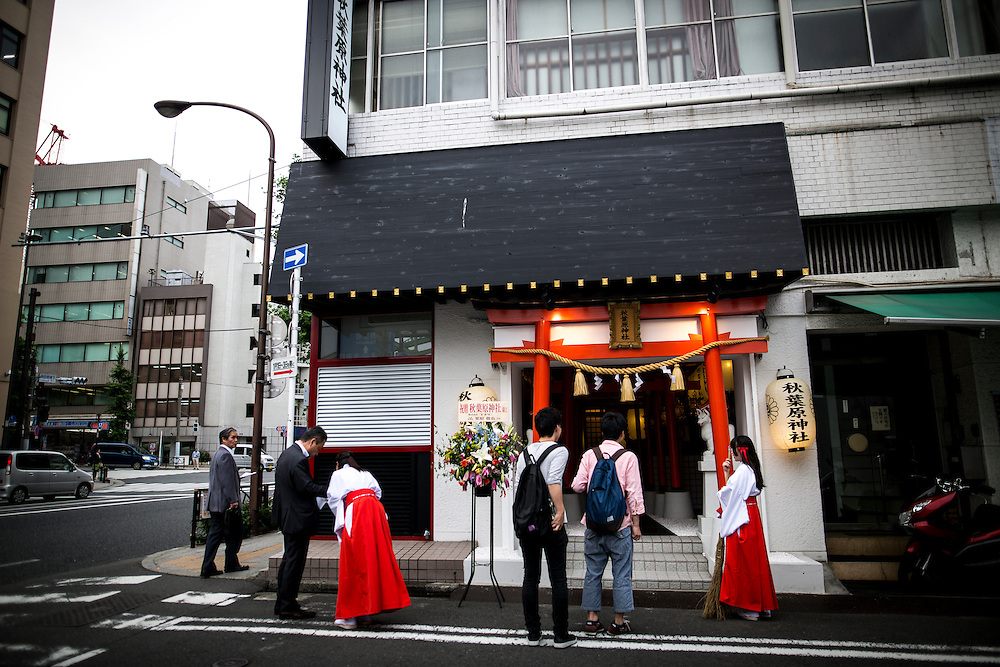 """TOKYO, JAPAN - JUNE 27 : A shrine maiden entertain guest in front of the entrance of Akihabara shrine in Akihabara, Tokyo, Japan. June 27, 2016.  A newly opened Akihabara Shrine offers a memorial services for """"deceased"""" anime figures. Photo by Richard Atrero de Guzman"""