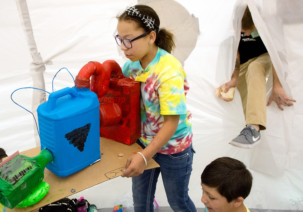 mkb041317a/metro/Marla Brose --  Kayla Munoz, a 5th grader at MacArthur Elementary, carries a model of a device that separates oxygen from carbon dioxide into a habitat, constructed with plastic and duct tape, during the annual Mission to Mars event at the Albuquerque Convention Center in Albuquerque, N.M., Thursday, April 13, 2017. The mission, organized by Air Force Research Lab's La Luz Academy, gives about 1,000 5th graders from around the state the task of colonizing Mars. Students built about 61 habitats after studying what is need to survive on Mars. (Marla Brose/Albuquerque Journal)