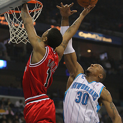 Jan 29, 2010; New Orleans, LA, USA; Chicago Bulls guard Derrick Rose (1) shoots over New Orleans Hornets forward David West (30) during the first half at the New Orleans Arena. Mandatory Credit: Derick E. Hingle-US PRESSWIRE