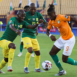 24 June 2019, Egypt, Cairo: Ivory coast's Wilfried Zaha (R) battles for the ball with South Africa's Kamohelo Mokotjo (C) and Thamsanqa Mkhize during the 2019 Africa Cup of Nations Group D soccer match between South Africa and Ivory coast at Al-Salam Stadium. Photo : PictureAlliance / Icon Sport
