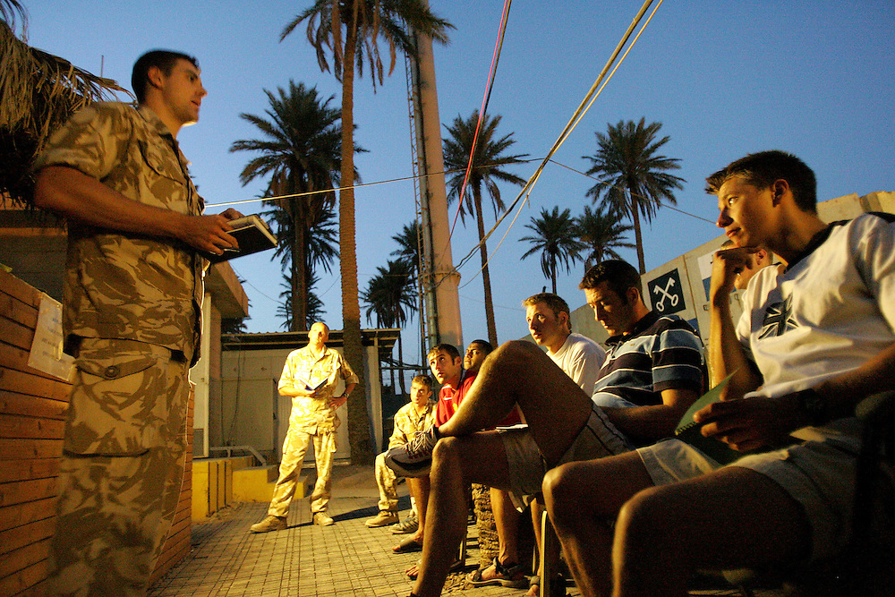 Baghdad, Iraq, 2 Oct 2005. Running 'Route Irish'...Lt Graham Rainey holds an evening briefing.....B Company, 1st Battalion, The Royal Irish Regiment, a tight-knit multi national fighting force make daily escorting runs along ?Route Irish?, the infamous Baghdad Airport road. The 46 man team are all British Army regulars but come from as far afield as Fiji, South Africa and Northern and Southern Ireland. Previous deployments in Kosovo, Sierra Leone and Northern Ireland have equipped them with the valuable skills needed to provide protection for British Forces and materials transiting the world?s most dangerous highway. Due to an increased presence of US forces along the route both in dug in positions and mobile patrols, attacks along the road have slackened, despite this a day rarely passed without an IED (improvised explosive device) being detonated or a small arms attack against coalition forces. ..The convoy attempts to maintain a seclusion ?bubble? around its vehicles for the duration of the journey. Any civilian vehicle that either strays into the bubble or refuses to keep their distance represents a threat and should they ignore the warning blasts on air horns carried in each vehicle the rules of engagement progress from warning shots to use of lethal force. The relative safety of the International Zone offers them an opportunity to decompress between missions. A duty driver ferries soldiers to the ?Liberty Pool?. Once only frequented by Iraq?s Ba?athist elite the luxury swimming pool and gym now fills with troops. Their body armour, helmets and weapons all within easy reach they either soak up the sun or compete with each other in diving competitions. After a daily briefing the troops have access to the ?Mosquito and Camel? bar where they watch TV or play pool and in accordance with the ?2 can rule? are allowed to drink 2 beers per night.