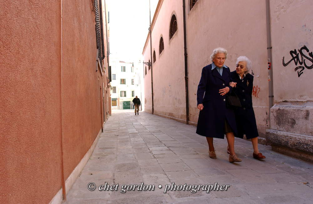 Two women make their way through the streets of Venice, Italy on Good Friday, March 29, 2002.