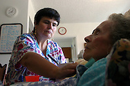 Healthcare worker helps an Alzheimer's patient  walk at a live-in residence for Alzheimer's and dementia related  patients.