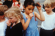 Kids in a school Playground, a girl sucking her thumb, UK 2000's