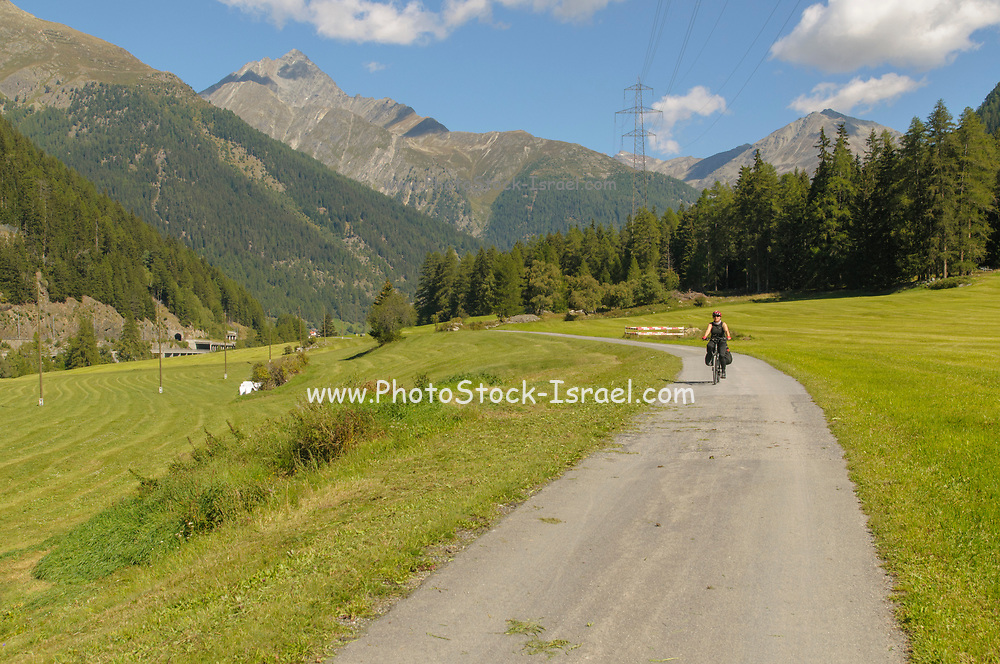 Female cyclist on the Inn Route near Susch (or Sus) Zernez, municipality in the district of Inn in the Swiss canton of Graubünden. Model release available