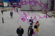 Seen through the purple swirls of graffiti marking the window of a bus driving through south London, a vaper exhales at Elephant & Castle, on 21st March 2019, in London, England.