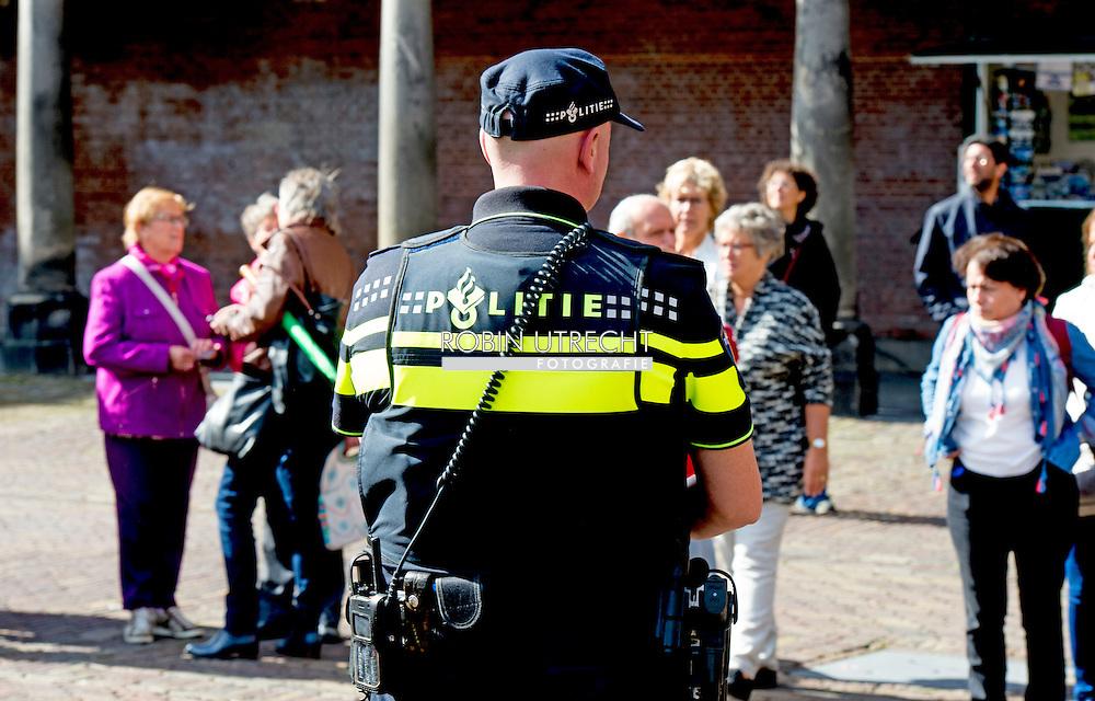 DEN HAAG - politiek , ridderzaal , Extra politie beveiling  en marechaussee op het binnenhof door de verhoogde dreiging . De kans op een aanslag in Nederland of op Nederlandse belangen in het buitenland blijft substantieel. Het dreigingsniveau is nu de op een na hoogste van de vier niveau&rsquo;s, minimaal, beperkt, substantieel en kritiek.  Een agent op straat . Politie marechaussee agenten surveilleren door het over het binnenhof en staan voor het tweede kamer gebouw . Bij de ingang van de Tweede Kamer staan marechaussees in plaats van politieagenten. De Koninklijke Marechaussee neemt beveiligingstaken over van de politie. De politieagenten kunnen zich daardoor meer richten op hun gewone taken. De bewaking van gebouwen vanwege terreurdreiging, waaronder ook Joodse instellingen, vergde veel politie-inzet. Opnieuw is het dreigingsniveau in Nederland vastgesteld op &lsquo;substantieel&rsquo;. Dat betekent dat de kans re&euml;el is dat er een aanslag in Nederland plaatsvindt. De grote diversiteit aan actoren en de manier waarop zij elkaar be&iuml;nvloeden maakt de dreiging complex. De recente aanslagen in Tunesi&euml;, Frankrijk en Koeweit laten zien dat de jihadistische dreiging diffuus is. Daarom is het belangrijk dat de professionele aandacht en inzet niet verslapt. Deze actuele ontwikkelingen worden meegenomen in de uitwerking en uitvoering van zowel het antiterrorismebeleid. Waar nodig zijn bestaande maatregelen verscherpt of aangepast. Dat staat in het Dreigingsbeeld Terrorisme Nederland (DTN), de beleidsreactie en de voortgangsrapportage van het Actieprogramma Integrale Aanpak Jihadisme die vandaag naar de Tweede Kamer zijn gestuurd.<br /> De gebeurtenissen in Frankrijk en Tunesi&euml; van afgelopen vrijdag 26 juni bevestigen het huidige dreigingsbeeld. Ook in Nederland en andere Westerse landen zijn soortgelijke aanslagen al langere tijd voorstelbaar. De daders en de doelen die zij kiezen worden steeds diverser. Samen met de oproepen van de leiding van IS en A