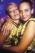 Two female clubbers with their arms round eachother, Ibiza 1998