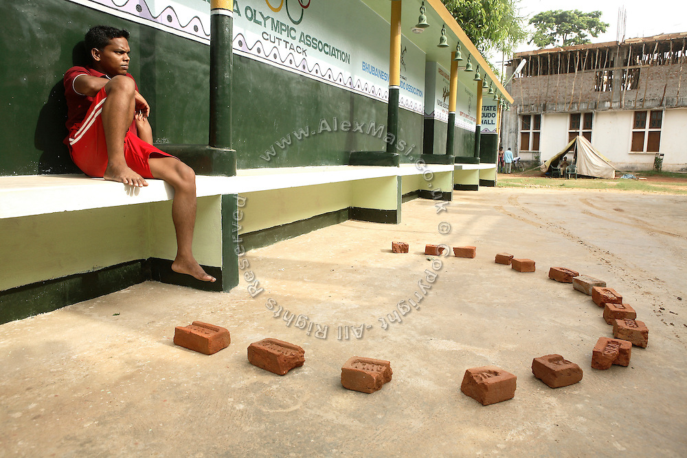 Kandan Murmu, 30, one of the trainers in Biranchi Das Judo Hall, is sitting in front of the spot where Biranchi, the coach of Budhia Singh, was recently shot, near the front entrance of the building, on Saturday, May 17, 2008. On May 1, 2006, Budhia completed a record breaking 65 km run from Jagannath temple, Puri to Bhubaneswar. He was accompanied by his coach Biranchi Das and by the Central Reserve Police Force (CRPF). On 8th May 2006, a Government statement had ordered that he stopped running. The announcement came after doctors found the boy had high blood pressure and cardiological stress. As of 13th August 2007 Budhia's coach Biranchi Das was arrested by Indian police on suspicion of torture. Singh has accused his coach of beating him and withholding food. Das says Singh's family are making up charges as a result of a few petty rows. On April 13, Biranchi Das was shot dead in Bhubaneswar, in what is believed to be an event unconnected with Budhia, although the police is investigating the case and has made an arrest, a local goon named Raja Archary, which is now in police custody. **Italy and China Out**