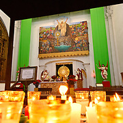 Votives in the foreground and religious artwork in the background at Iglesia de San Francisco in Antigua, Guatemala.