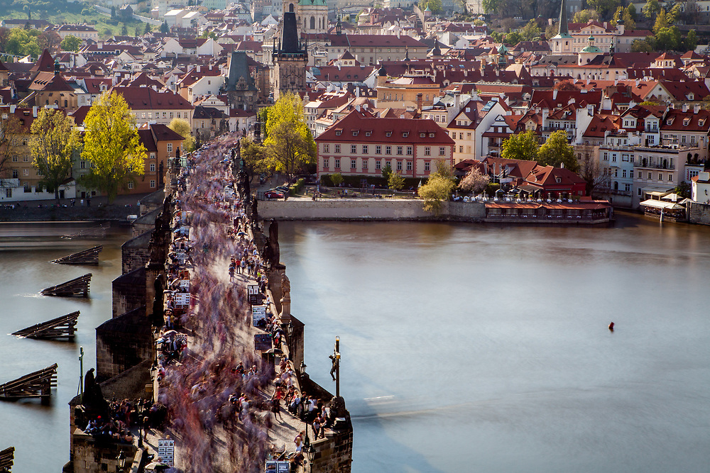 """Crowds are moving across Charles Bridge seen from The Old Town Bridge Tower which is one of the most beautiful Gothic gateways in the world. In the back Prague's """"Lesser Town"""" (Mala Strana)."""
