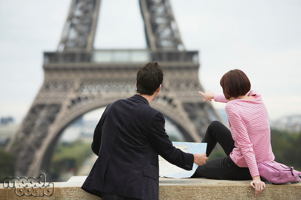 France Paris couple looking at map in front of Eiffel Tower back view