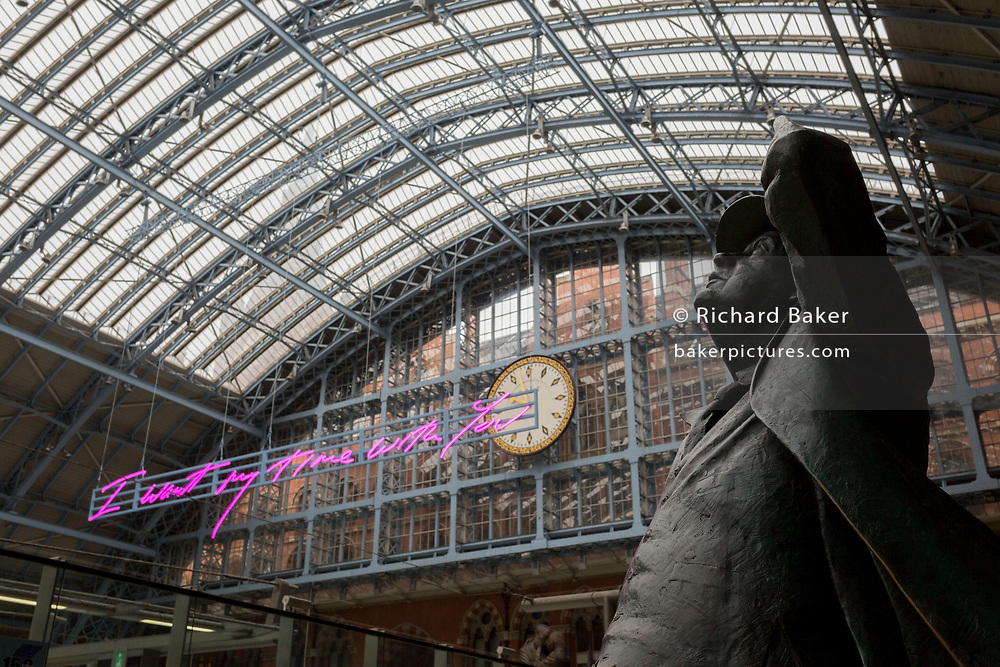 "The statue of poet John Betjeman by Martin Jennings looks up to the new artwork entitled 'I Want My Time With You' by British (Britpop) artist Tracy Emin which hangs over the main concourse at St. Pancras Station, on 10th April 2018, in London, England. In the sixth year of the Terrace Wires Commission - and in celebration of the 150th anniversary of St Pancras International and the 250th anniversary of the Royal Academy of Arts, at one of London's mainline station, the London hub for Eurostar - the 20 metre-long greeting to commuters reads 'I Want My Time With You' and Emin thinks that arriving by train and being met by a lover as they put their arms around them, is very romantic."" The Brexit-opposing artist also said she wanted to make ""a statement that reaches out to everybody from Europe arriving in to London""."