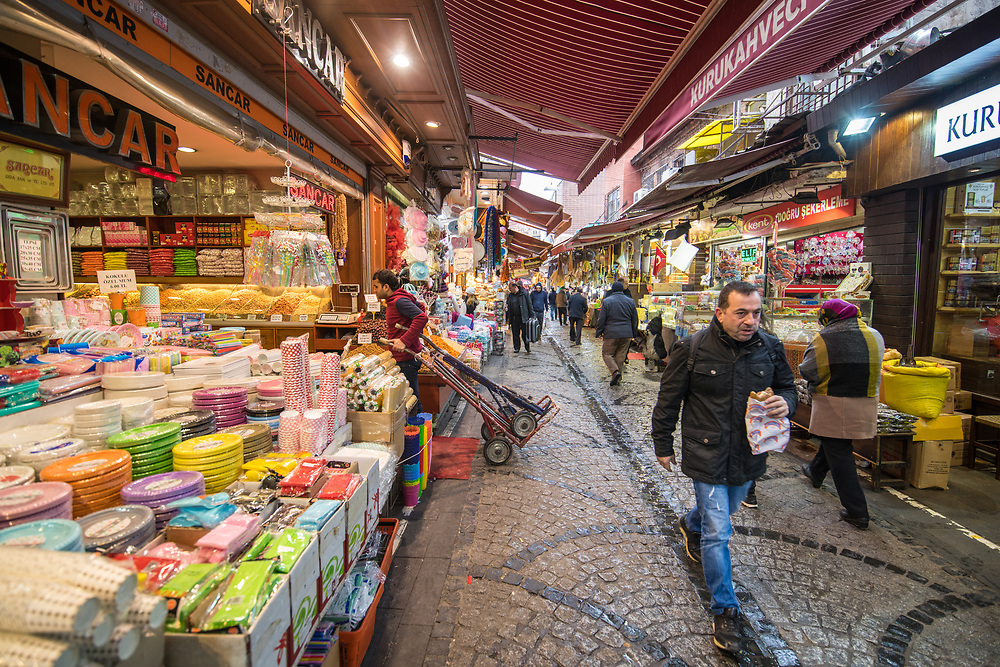 Shoppers walk along narrow street lined with shops selling a variety of goods and spices, Istanbul, Turkey