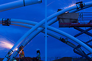 Ironworkers grinding welds on a decorative arches at dusk
