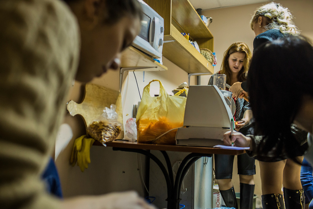 DNIPROPETROVSK, UKRAINE - NOVEMBER 16, 2014:  Zhanna Kuzmytska, 23, a psychologist, left, peels carrots as  Alyona Fedorenko, 36, an economist, and Tatyana Sirko, 42, a gynecologist, right, shred them for traditional borscht soup in the kitchen at the Dnipropetrovsk Volunteer Logistics Center, a charity organization that produces supplies for pro-Ukrainian fighters battling rebels in the country's East, in Dnipropetrovsk, Ukraine. CREDIT: Brendan Hoffman for The New York Times