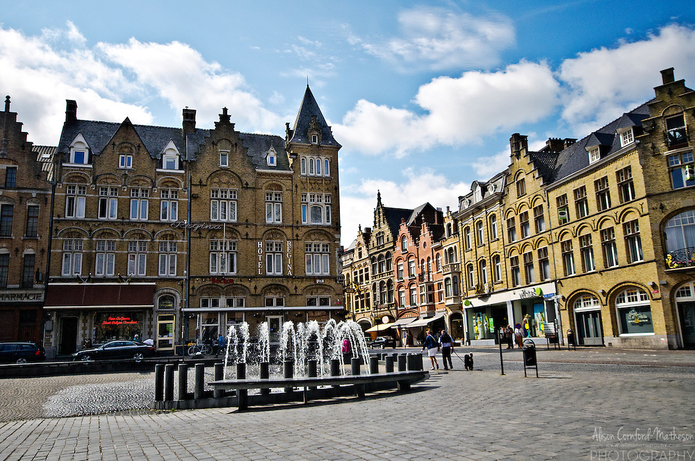 The Grote Markt or town square of Ypres Belgium is dominated by a large belfry and surrounded by shops and restaurants