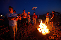 21 June 2008:  Friends gather around a wood burning beach bonfire at tower 9 in Huntington Beach, CA.