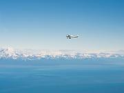 A tourist airplane flies over the Cook Inlet, Alaska towards Lake Clark National Park.
